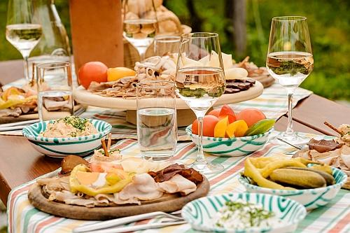 Hagyományos Heuriger ételek egy csodásan megterített asztalon: parasztszalonna, véres hurka, füstölt hús, májkrém, liptói sajt, ami mellé persze dukál a helyi bor is