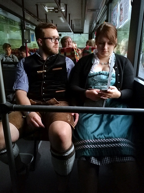 Fiatal pár a helyi partibuszon, amely egész a fesztivál ideje alatt szállítja a sörfesztivál látogatóit. Természetesen népviseletben.